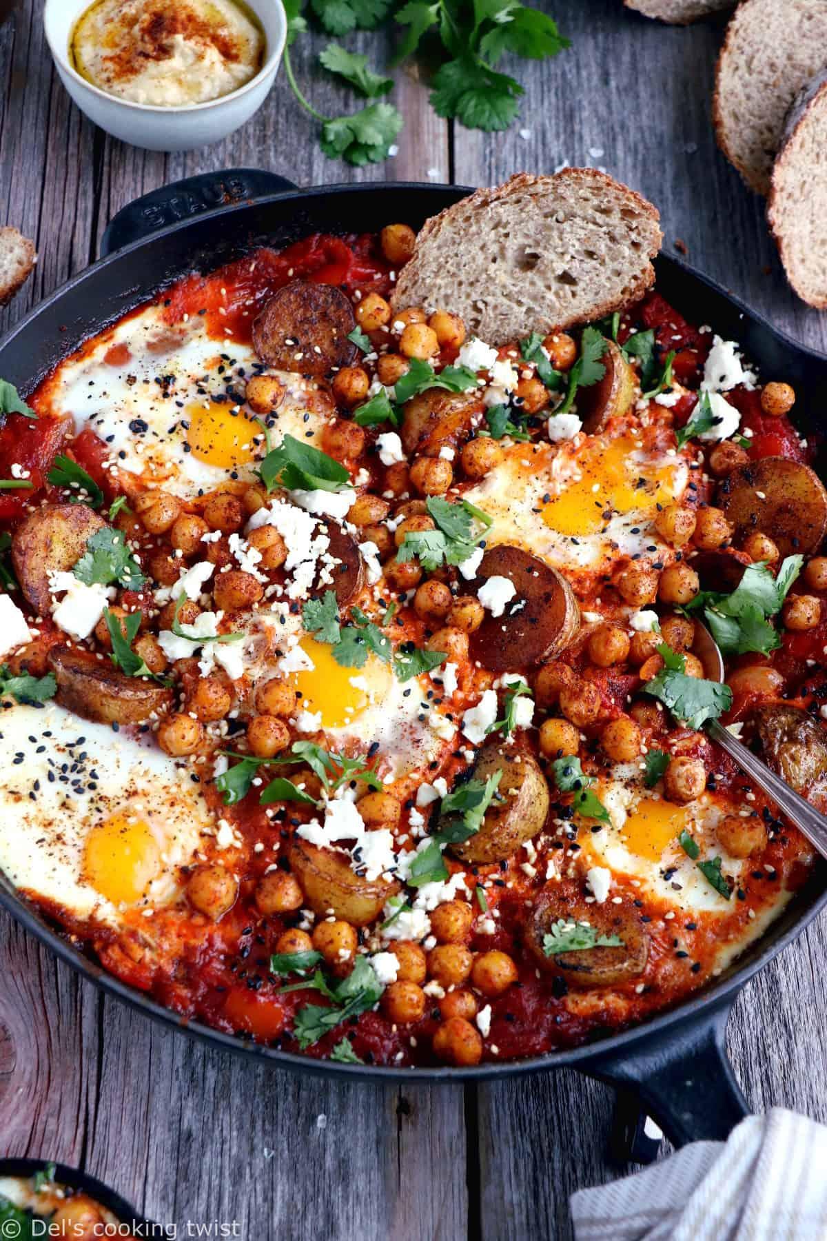 Une shakshuka en version deluxe, avec une base d'oeufs pochés plongés dans une sauce tomate aux oignons, le tout réhaussé de pommes de terres et pois chiches épicés.