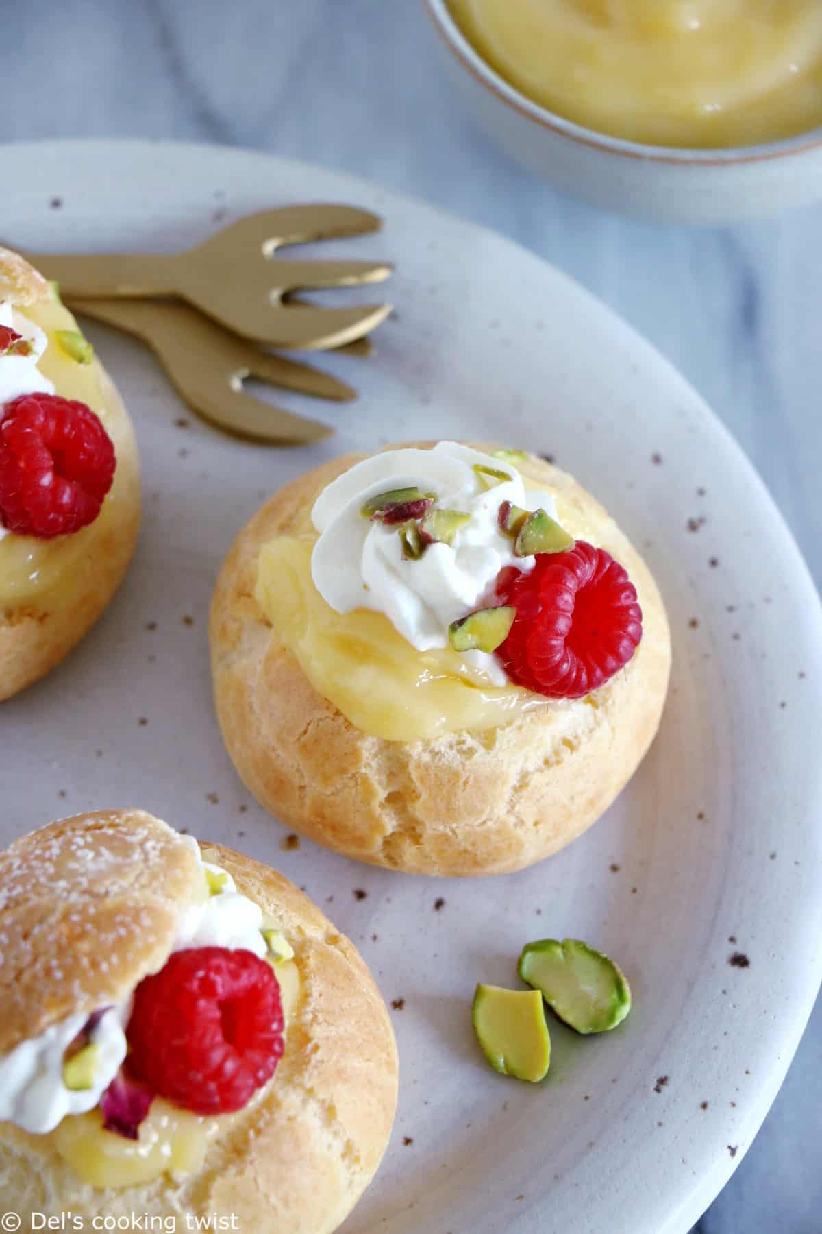 Easy raspberry and lemon curd cream puffs make a delicious fancy sweet dessert with a lovely touch of acidity brought by the homemade lemon curd and the fresh raspberries.