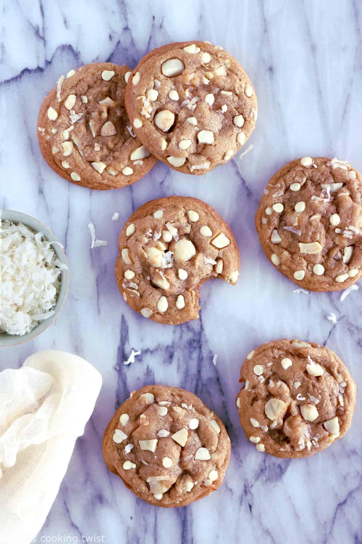 Cookies au chocolat blanc, noix de coco et noix de macadamia. Plongez dans la douceur de ces cookies au chocolat blanc, noix de coco et noix de macadamia à la texture à la fois souple et légèrement croustillante sur les côtés. Amoureux de chocolat blanc, cette recette est pour vous !