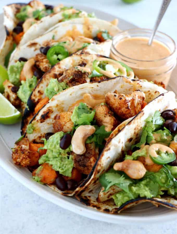Spicy Vegan Sweet Potato and Cauliflower Tacos. Healthy vegan tacos filled with roasted sweet potato and cauliflower, mashed avocado and topped with a spicy cashew sauce. They are loaded with healthy and hearty flavors and make a perfect, quick, and easy weeknight dinner. These tacos are Oh SO good!