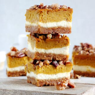 These amazing pumpkin cheesecake bars with candied pecans are delicious and so EASY to make! Full of fall spices, the 4 layers come easily together in a sumptuous dessert that is sure to impress at any holiday gathering.