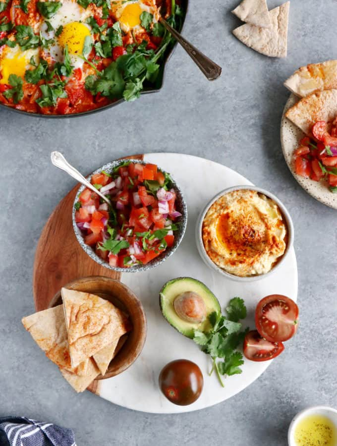 Ever wondered how to serve a shakshuka? Place it in the center of the table and serve with various small plates, breads and salads to make this meal a feast!
