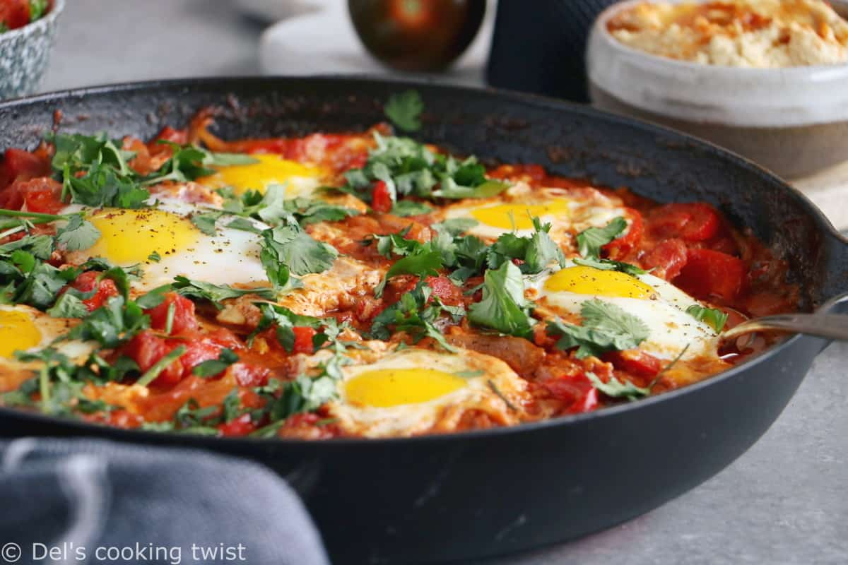 Shakshuka with Feta Cheese is a simple dish consisting of poached eggs in a simmering tomato sauce with feta and spices, traditionally served in a cast iron skillet.