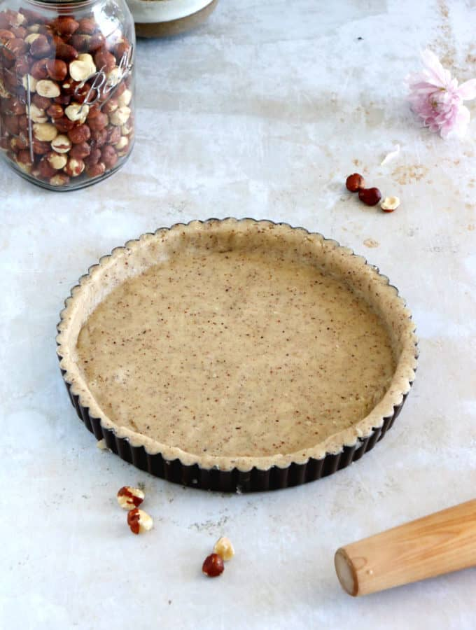 Hazelnut pie crust is a sweet shortcrust pastry prepared with ground hazelnuts. The dough comes together easily with just a few ingredients and has a subtle nutty flavor.